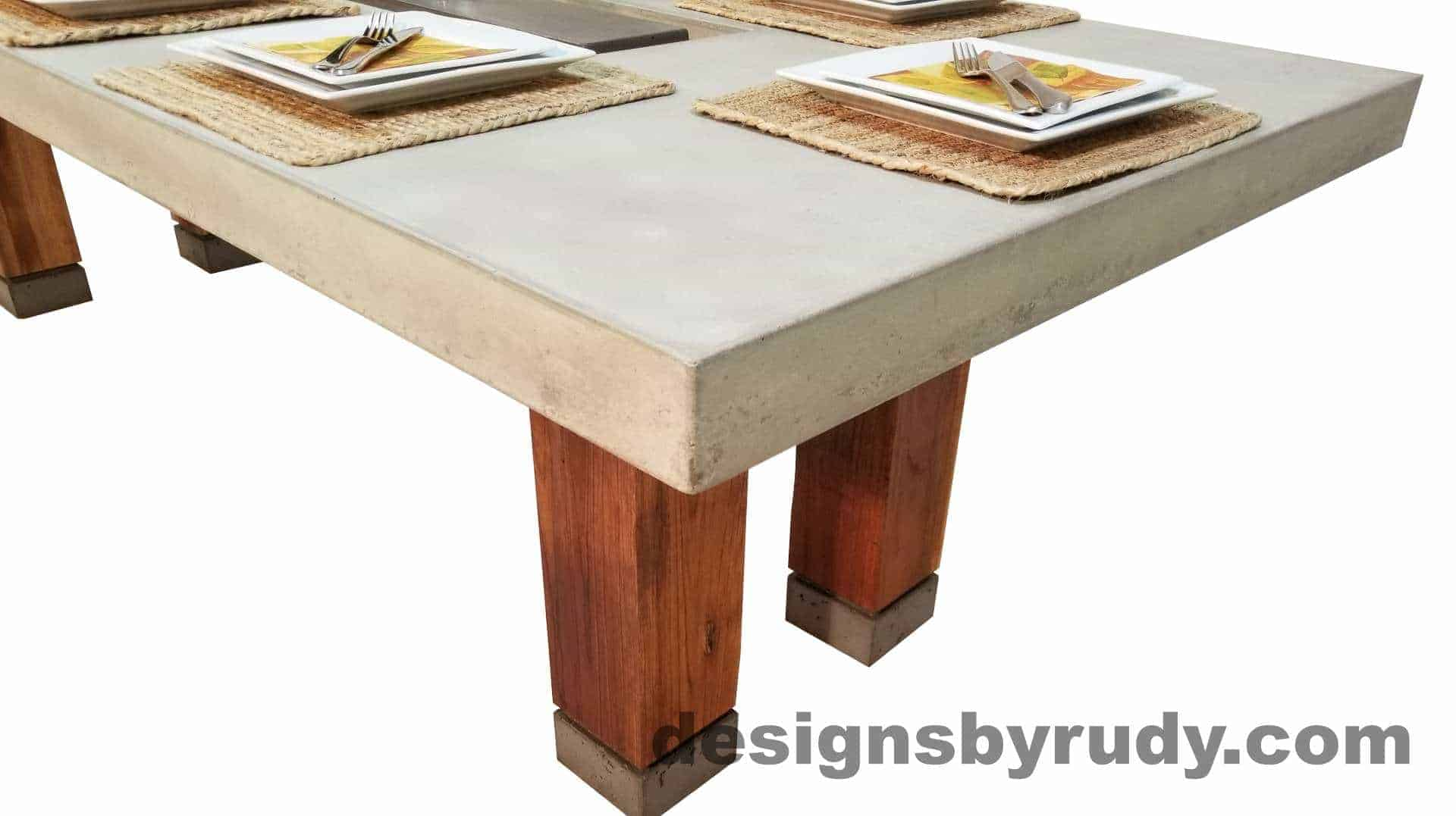 Concrete top dining table on teak legs with center serving tray - corner closeup view, Designs by Rudy