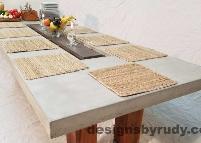Concrete top dining table on teak legs with center serving tray -long view with mats, Designs by Rudy