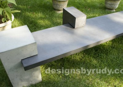 DR CB1 concrete bench on 3 pedestals by Designs by Rudy, garden, natural light, top angle 2 pedestals closeup view
